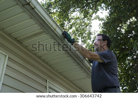 Cleaning gutters of leaves and sticks on a home.  - stock photo