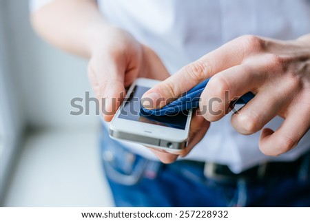cleaning her smart phone screen