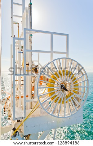 Cleaning hose and equipments on a cruise ship against a blue sky and sea. - stock photo