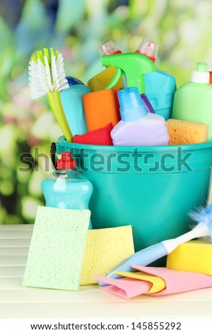 Cleaning items in bucket on bright background - stock photo