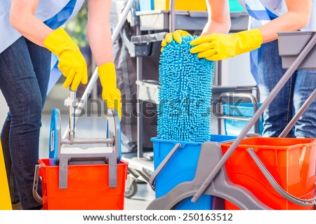 Cleaning ladies mopping floor, close up on hands and tools - stock photo