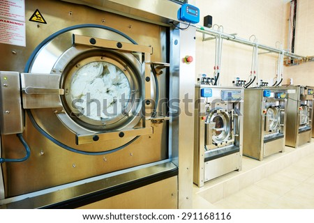 cleaning services. industrial laundry washing machine with cloth - stock photo