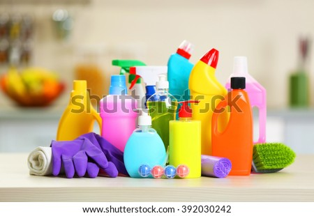 Cleaning set with products and tools on kitchen table - stock photo