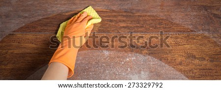 Cleaning soiled parquet in gloves with yellow rag - stock photo