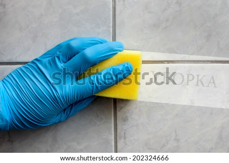 Cleaning sponge held in hand while cleaning bathroom with russian lettering (cleaning in english translation) - stock photo
