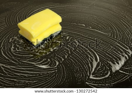 cleaning sponge with white foam laying on black glassy stove - stock photo