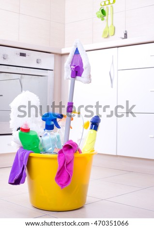 Cleaning supplies and equipment on kitchen floor with oven in background