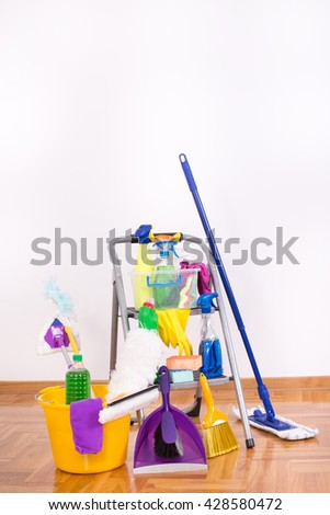 Cleaning supplies and equipment on ladder on parquet in the room