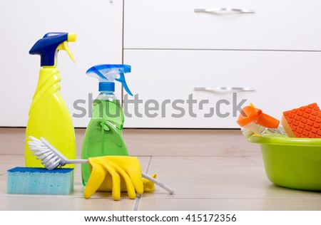 Cleaning supplies and equipment on the tiled floor in the kitchen - stock photo