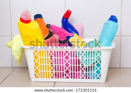 cleaning supplies in plastic box on tiled floor in bathroom - stock photo