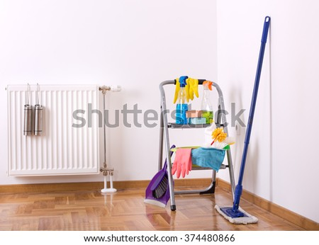 Cleaning supplies on ladder and mop and brush with dustpan on the parquet in the corner of room - stock photo