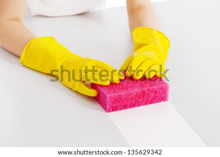Cleaning table with pink sponge and protective glove