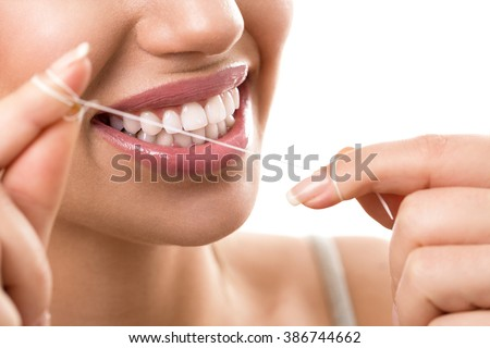 Cleaning teeth with dental floss, perfect healthy tooth - stock photo