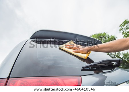 Cleaning the car glass with microfiber cloth