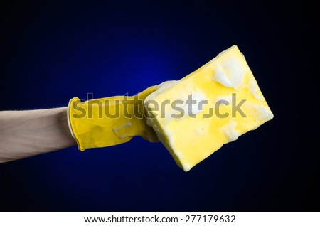 Cleaning the house and sanitation topic: Hand in yellow rubber glove holding a yellow sponge wet with foam on a dark blue background in studio - stock photo