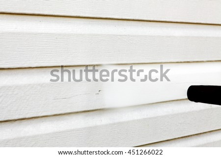cleaning the house (vinyl siding) high pressure cleaner - stock photo