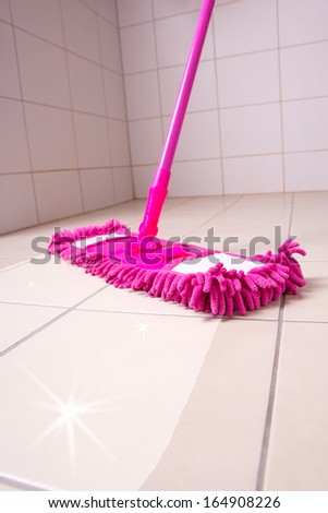 cleaning the tiled floor with pink mop - stock photo