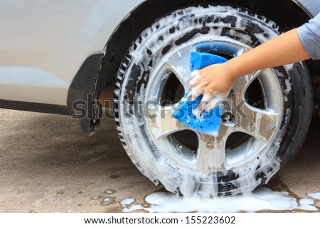 cleaning the wheel car wash with a sponge - stock photo