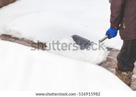 cleaning the yard of snow. A man in a jacket and boots, holding a plastic shovel with snow