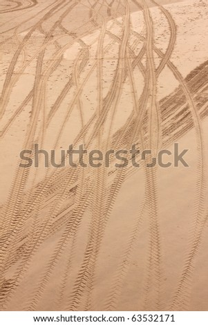 Cleaning tractor tyre imprint on beach - stock photo