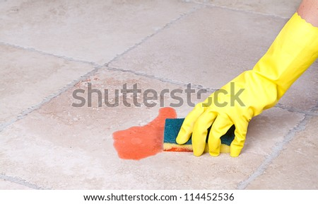 Cleaning up juice spill  on tile floor with sponge - stock photo