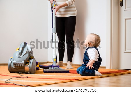 Cleaning up the room together - mother and her baby  with vacuum cleaner - stock photo
