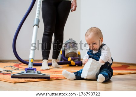 Cleaning up the room - woman with vacuum cleaner, baby sitting on floor - stock photo