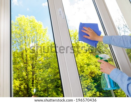 cleaning vinyl plastic window on a background blue sky - stock photo