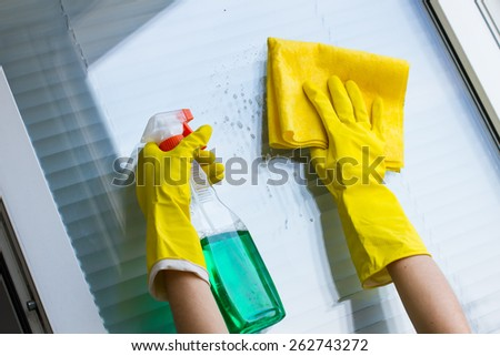 Cleaning windows with special rag and detergent in yellow gloves