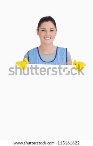 Cleaning woman showing a white panel on the white background - stock photo