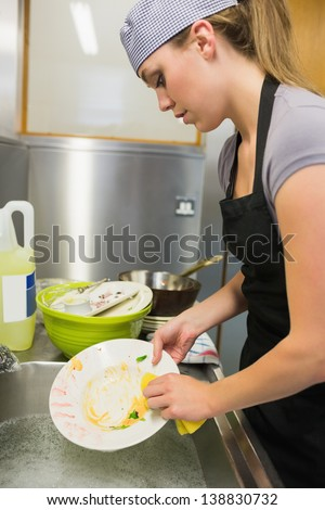 Cleaning woman washing the dishes in the restaurant - stock photo