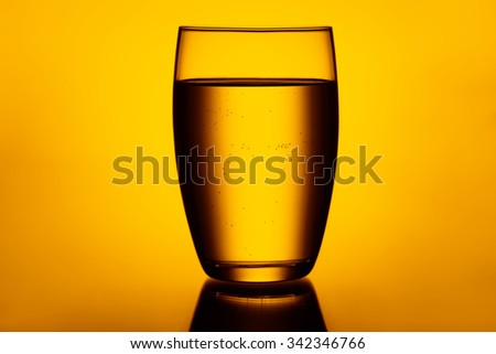 Clear and full glass of water orange yellow red colors  - stock photo