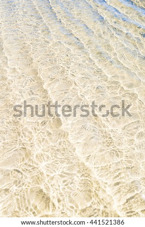 Clear and shallow sea water with light sandy soil; Gentle waves on the shallow water; Wavy water surface for background; Cooling for the feet; Beach impressions - stock photo