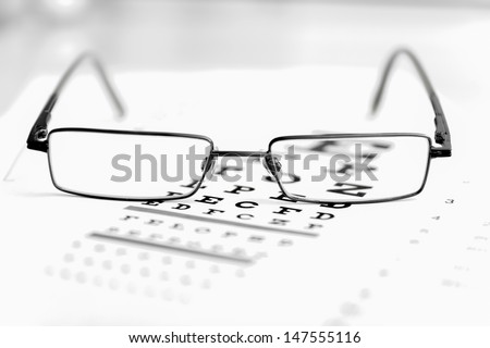 Clear Black modern glasses on a eye sight test chart. - stock photo