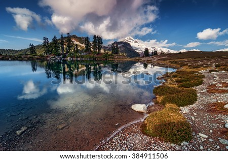 Clear, blue lake with a reflection of the mountain and pine trees, snow-covered mountain afar, mountain side meadow