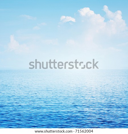 Clear blue sea surface with ripples and sky with fluffy clouds - stock photo