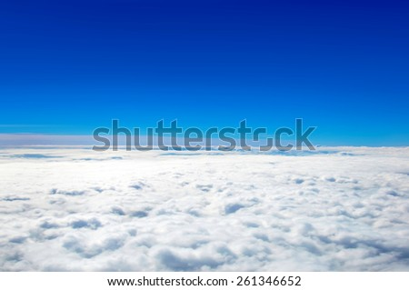 Clear blue sky above cloud layer - soft focus - stock photo