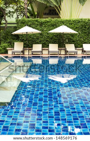 Clear blue swimming pool close up in tropical garden - stock photo
