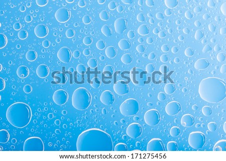 Clear blue water drops over blue background