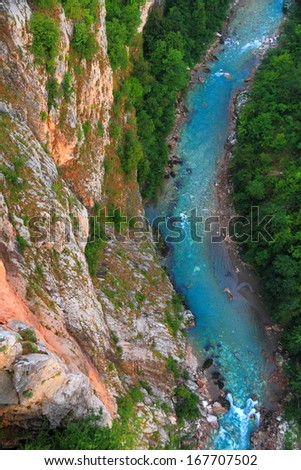 Clear blue water flowing at the bottom of a deep canyon - stock photo