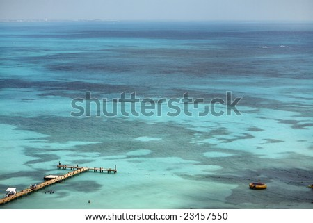 Clear, blue waters in a tropical setting with a pier going out to the water