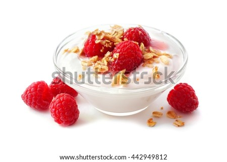 Clear bowl of raspberry flavored yogurt with granola and berries over a white background