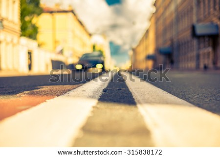 Clear day in the big city, the lights of the approaching car. View of the road at the level of the dividing line, image in the yellow-blue toning - stock photo