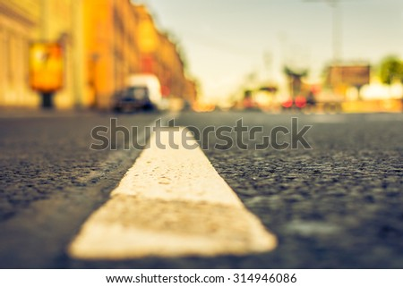 Clear day in the big city, the lights of the approaching cars. View of the road at the level of the dividing line, image in the yellow-blue toning - stock photo