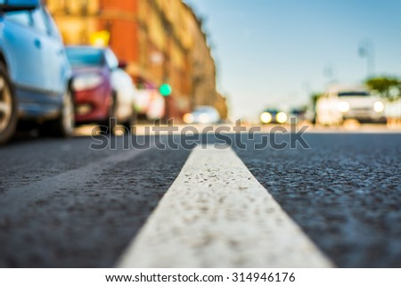 Clear day in the big city, the lights of the approaching cars. View of the road at the level of the dividing line - stock photo