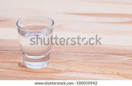 Clear drink on wood table. - stock photo