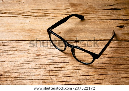 Clear Eyeglasses Glasses with Black Frame Fashion Vintage Style on Wood Desk Background, Rustic Still Life Style. - stock photo