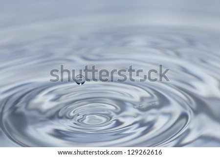 clear fresh water drop falling in a big basin - stock photo