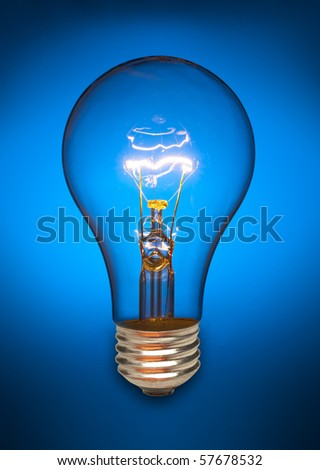 Clear light bulb back lit by a blue light and turned on - stock photo