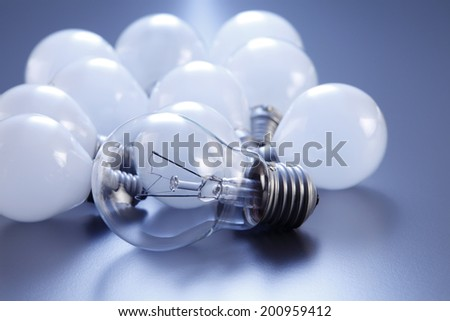 clear light bulb standing up from others